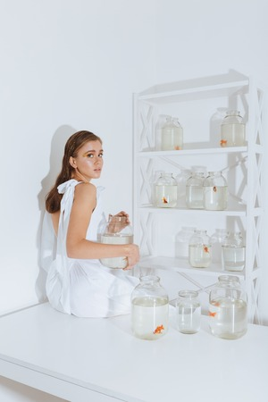 aquarist: Pretty young woman sitting on white table with gold fishes in jars in the room