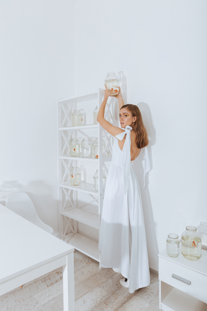 gold fish bowl: Beautiful young woman standing and putting jar with gold fish on the shelf in the room