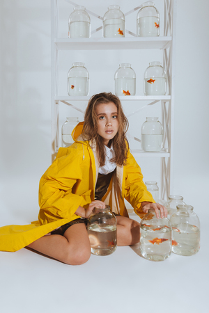 fishtank: Beautiful young woman in yellow raincoat sitting and holding jars with gold fishes