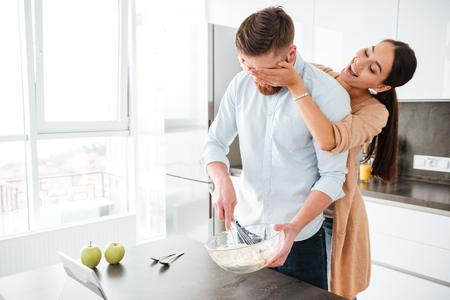 Funny couple cooked in kitchen. girl closes her eyes Stock Photo