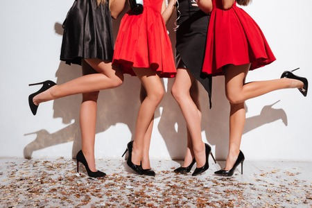 Close-up van benen van vrouwen die zich op de vloer met confettien bevinden en partij over witte achtergrond hebben Stockfoto