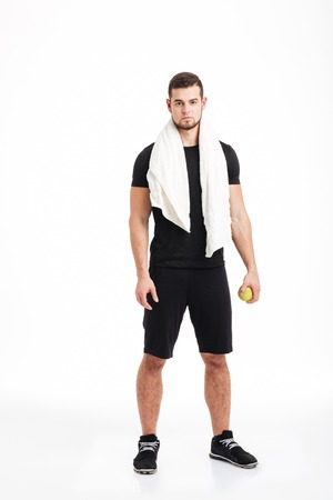 Fitness man with towel. full length portrait in studio. isolated white background