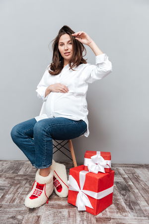 full lenght: Photo of pregnant woman with gifts. full lenght. looking at camera