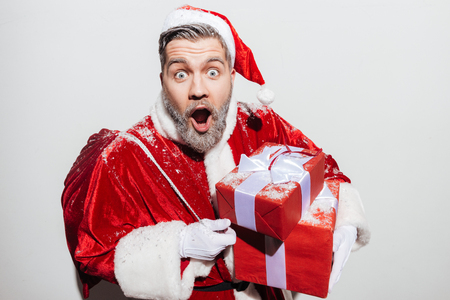 Astonished man santa claus with persent boxes and gift sack