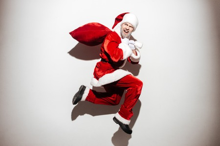 Cheerful bad man santa claus holding gift sack and running over white background Stock Photo