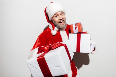 hat new year s eve: Happy man santa claus holding present boxes and laughing Stock Photo