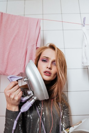 Portrait of attractive young womna with vintage iron in bathroom Stock Photo