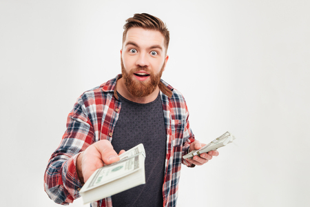 Casual bearded man in plaid shirt giving money to camera over white background