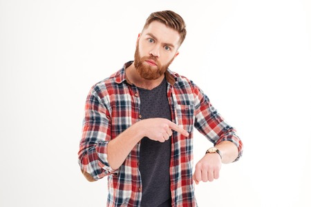 Handsome young casual bearded man pointing on watch over white background
