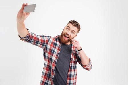 Gelukkige jonge toevallige man zelfie foto over witte achtergrond