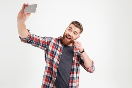 Glücklicher junger zufälliger Mann , der selfie Foto über weißem Hintergrund nimmt