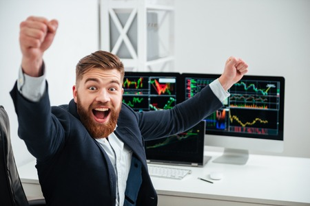 immersed: Cheerful excited young businessman with raised hands shouting and celebrating success at workplace in office Stock Photo