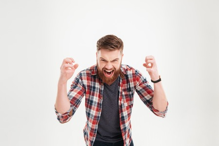 Portrait of a casual angry man screaming with raised arms isolated on a white background Stock Photo