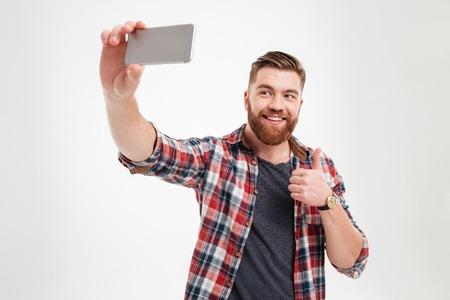 Ritratto di un uomo barbuto allegro che prende selfie e che mostra i pollici aumenta il gesto sopra fondo bianco