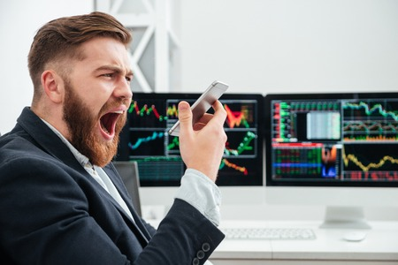 Angry irritated bearded young businessman screaming in smartphone in office Stock Photo