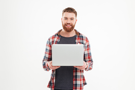 Happy smiling bearded man holding laptop and looking at camera over white background