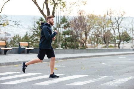 full lenght: Runner. runs on the street. on crosswalk. full lenght. front photo Stock Photo