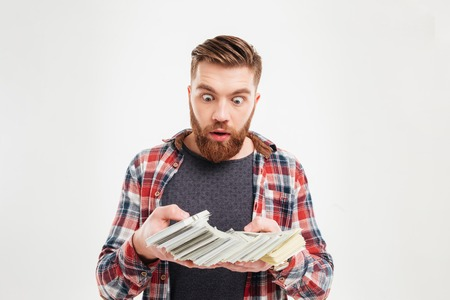 eyes wide open: Excited young bearded man in plaid shirt looking at money banknotes with eyes wide open isolated on a white background Stock Photo