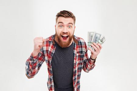 Alegre hombre barbudo en camisa a cuadros celebración de billetes de dólar sobre fondo blanco Foto de archivo
