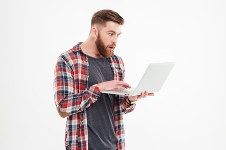 Surprised young bearded man in plaid shirt looking at laptop over white background