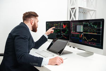 ハンサムな青年実業家座っていると、オフィスのコンピューターでの作業 写真素材