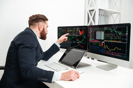 Handsome young businessman sitting and working with computer in office