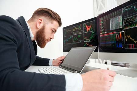 Concentrated young businessman working with computer in office