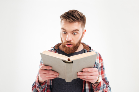 eyes wide open: Young beraded man looking in book with eyes wide open over white background