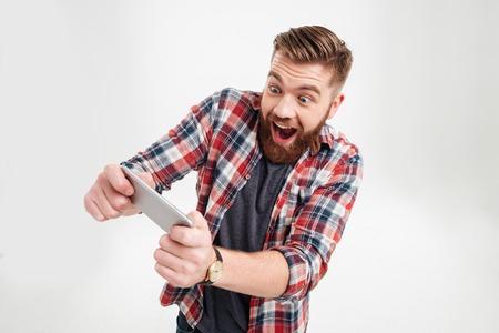 Excited hombre barbudo en camisa a cuadros jugando en el teléfono inteligente sobre fondo blanco