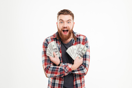 Happy young bearded man in plaid shirt holding dollar bills over white background