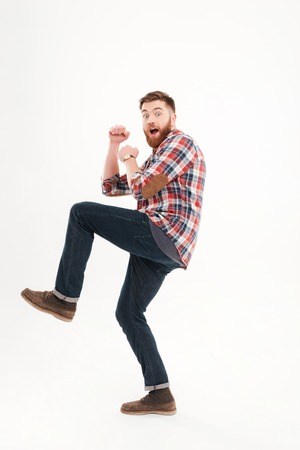 Scared frightened young man holding fists in front of himself over white background Stock Photo