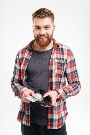 Lachend gelukkig bebaarde man in geruite overhemd om geld in zijn portemonnee op een witte achtergrond Stockfoto
