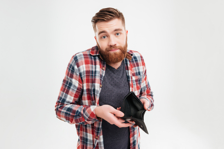 Upset young bearded man in plaid shirt holding empty wallet over white background Stock Photo
