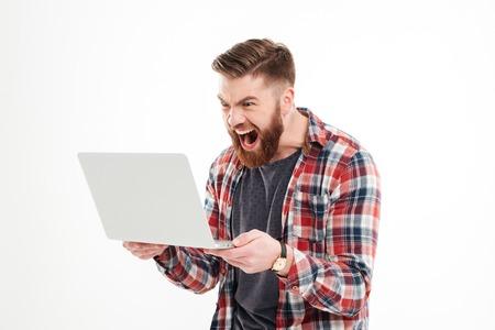 怒れる若者たちのひげを生やしたホワイト バック グラウンドで叫んで手のラップトップに格子縞のシャツの男