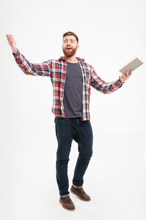 Full length portrait of a young bearded man actor in plaid shirt holding book and gesturing with hands over white background
