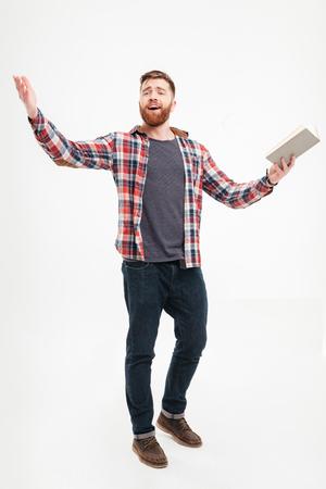 Full length portret van een jonge bebaarde man acteur in plaid shirt bedrijf boek en gebaren met de handen over witte achtergrond Stockfoto