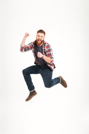 Positive cheerful carefree casual young man in plaid shirt jumping in the air and smiling Stock Photo