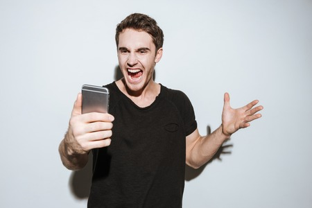 agressive: Image of young angry man dressed in black t-shirt standing over white background and using phone.