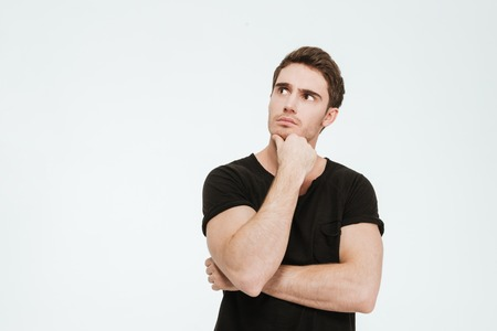 Picture of young thoughtful man dressed in black t-shirt standing over white background looking aside. Stockfoto