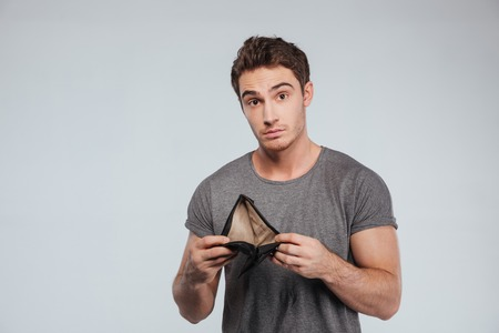 afflict: Upset young man holding empty wallet over white background