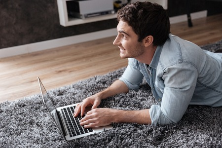look pleased: Close up portrait of a man using laptop while lying on carpet at home Stock Photo