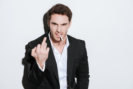agressive: Image of agressive businessman posing at studio and look at camera while holding cigarette and showing middle finger. Isolated over white background.
