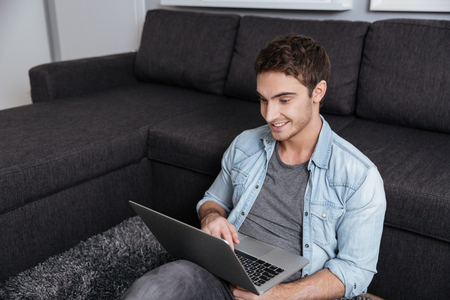 look pleased: Smiling casual man sitting on carpet with laptop computer at home Stock Photo