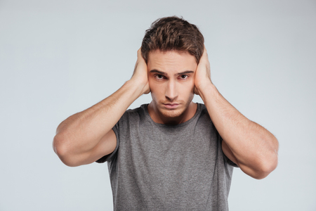 hands covering ears: Portrait of a serious young man covering both ears with hands isolated on the gray background
