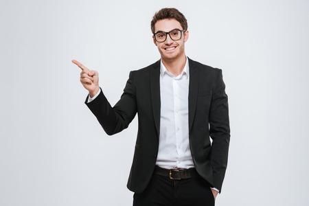 指離れてオーバー ホワイト バック グラウンドを指している眼鏡の幸せなビジネスマンの肖像画