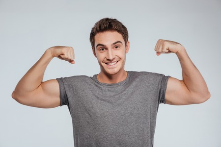 Portrait of a smiling srtong man flexing biceps isolated on the gray background