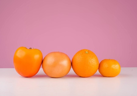 Fresh fruit mandarin, persimmon Sharon, tangerine and orange on a table isolated on a pink background