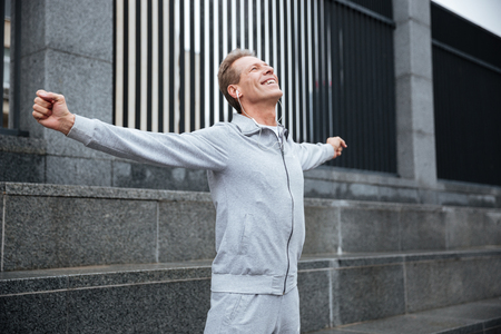 one people: Happy Runner in gray sportswear and headphone warming up on the street with hands to the side. Side view