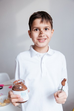 spreaded: Portrait of cheerful little boy eating chocolate spread from jar by spoon