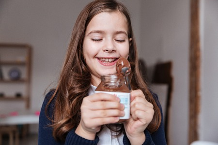 Cheerful little girl eating chocolate spread from jar by spoon and having fun